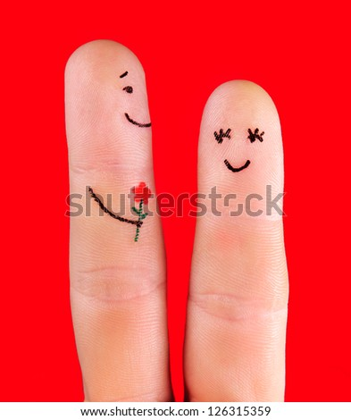 happy couple concept - a man with flower and a woman,painted at fingers isolated on red background - stock photo
