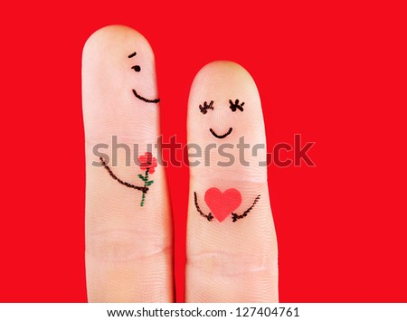 happy couple concept - a man with flower and a woman,painted at fingers isolated on red background