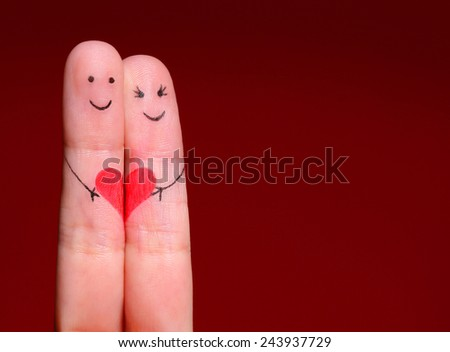Happy Couple Concept. Two fingers in love with painted smiley faces and heart over red background - stock photo