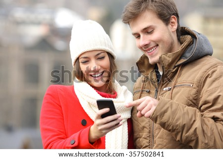 Happy couple consulting a smart phone in winter in the street - stock photo