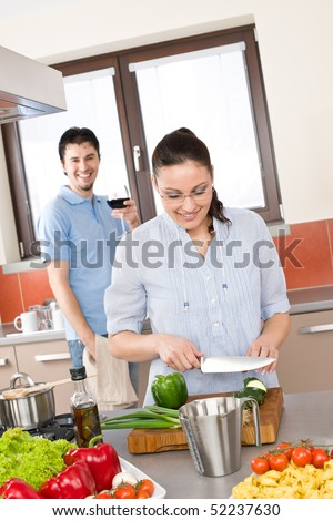 Happy couple cook in modern kitchen, woman cutting vegetable