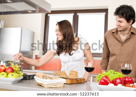 Happy couple cook together in modern kitchen, drink red wine - stock photo