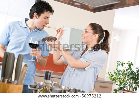 Happy couple cook together in modern kitchen tasting food, drink red wine - stock photo
