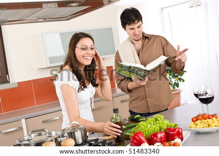 Happy couple cook together in modern kitchen with cookbook - stock photo