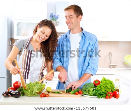 Happy Couple Cooking Together - Man and Woman in their Kitchen at home Preparing Vegetable Salad.Diet.Dieting. Healthy Food - stock photo