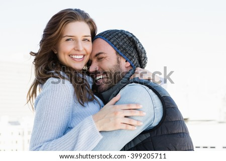 Happy couple cuddling each other and smiling outdoors - stock photo