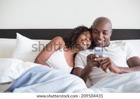 Happy couple cuddling in bed with smartphone at home in the bedroom - stock photo