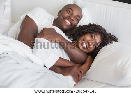 Happy couple cuddling together in bed at home in the bedroom - stock photo