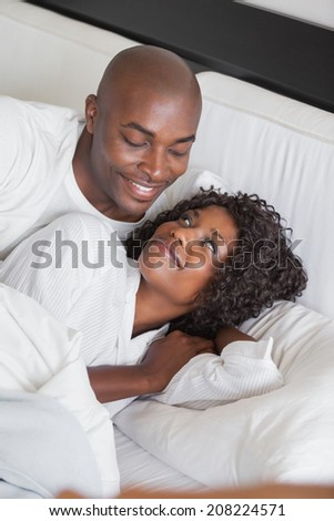 Happy couple cuddling together in bed at home in the bedroom