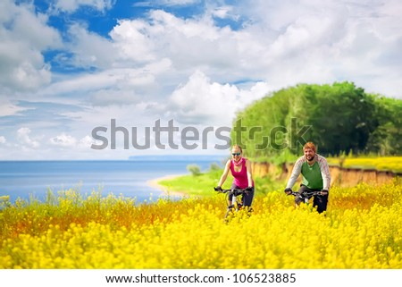 happy couple cycling in canola fields - stock photo