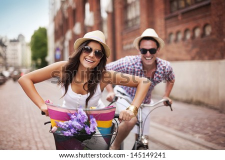 Happy couple cycling in the city - stock photo