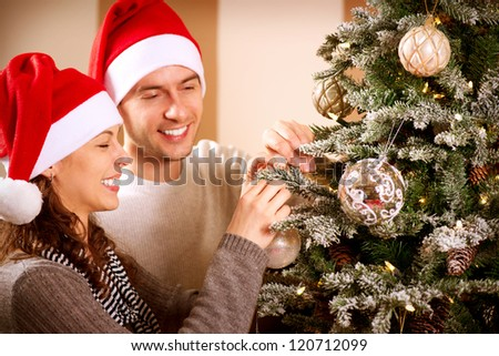 Happy Couple Decorating Christmas Tree in their Home. Smiling Man and Woman together Celebrating Christmas or New Year. Christmas Tree Decoration.Family - stock photo