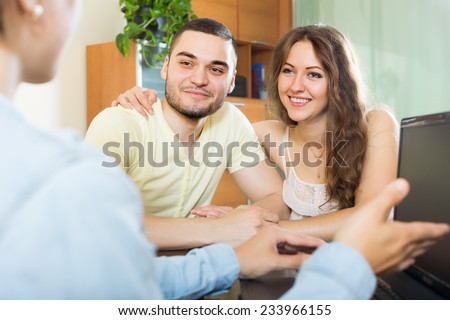happy couple discussing details of private insurance with agent at table - stock photo