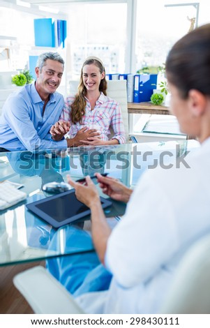 Happy couple discussing with doctor in clinic - stock photo