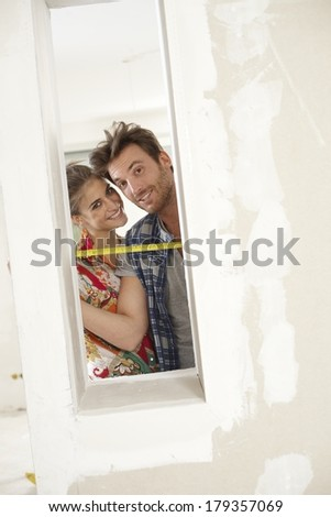 Happy couple DIY at home renovation, smiling, looking through window. - stock photo