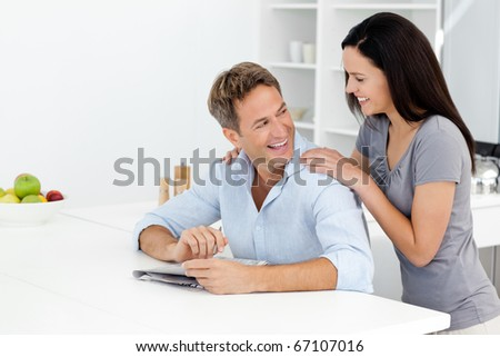 Happy couple doing a cryptic crossword together in the kitchen - stock photo