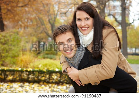 Happy couple doing a piggyback ride in a fall park - stock photo