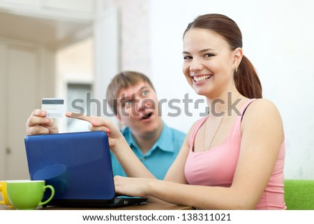 happy couple doing shopping in internet with credit card at home - stock photo