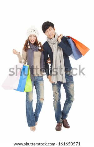 Happy couple doing shopping with winter clothing - stock photo
