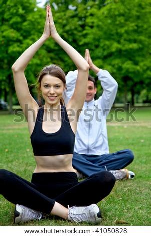 Happy couple doing yoga on the park - stock photo