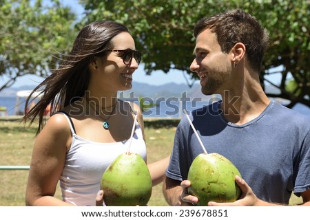 Happy couple drinking coconut water - stock photo