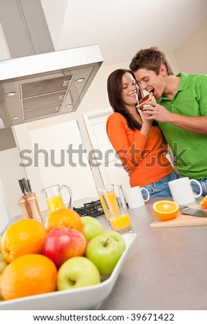 Happy couple drinking coffee in the kitchen together