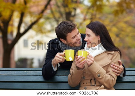 Happy couple drinking tea in a fall park - stock photo