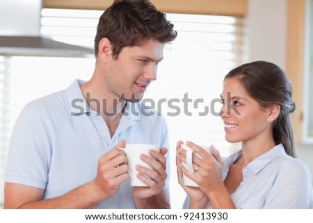 Happy couple drinking tea while looking at each other - stock photo