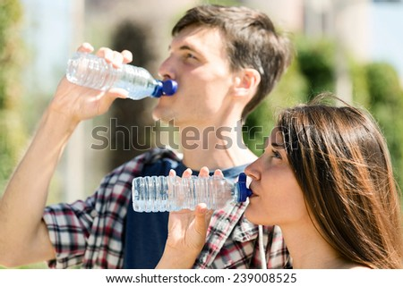 Happy couple drinking water from plastic bottles outdoor - stock photo