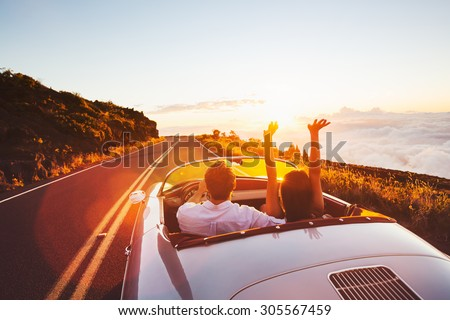 Happy Couple Driving on Country Road into the Sunset in Classic Vintage Sports Car  - stock photo