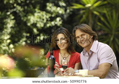 happy couple eating in the garden - stock photo