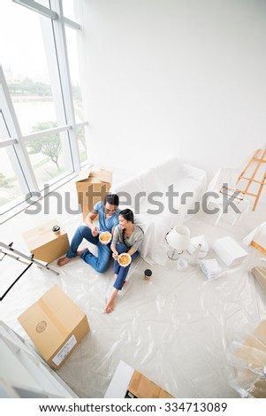 Happy couple eating noodle soup after moving in new apartment - stock photo