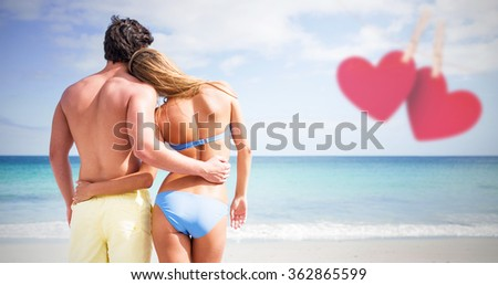 Happy couple embracing and looking at the sea against hearts hanging on a line - stock photo