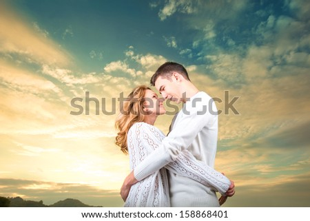 Happy couple embracing and watching one another under the sunny sky - stock photo
