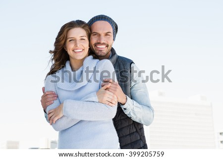 Happy couple embracing each other and smiling outdoors - stock photo