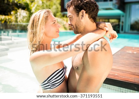 Happy couple embracing in the pool and looking at each other - stock photo