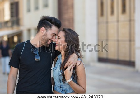 Happy couple embracing leaning on each other head laughing