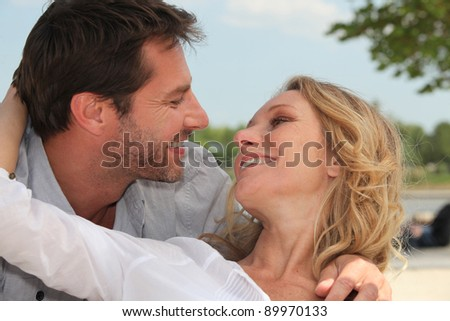 happy couple embracing on the beach - stock photo