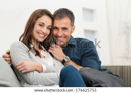 Happy Couple Embracing Sitting On Couch Looking At Camera - stock photo