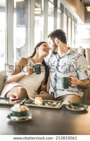 Happy couple enjoying a coffee at the coffee shop cafe Young adult man and woman kiss touch nose each other against window glass in perspective Romantic relationship Pair hold green mug in hands - stock photo