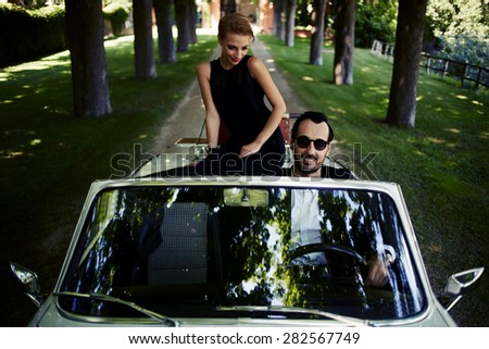 Happy couple enjoying a ride on their luxury convertible in the summer,gorgeous rich woman feels so glad while they riding on cabriolet with sure handsome brunette man, romantic couple at journey trip  - stock photo