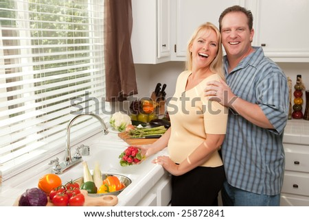 Happy Couple Enjoying An Eveing Preparing Food in the Kitchen. - stock photo