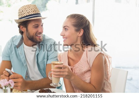 Happy couple enjoying coffee and cake at the coffee shop - stock photo