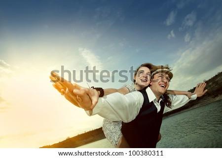 Happy couple enjoying flying over the sea, female on man's back - stock photo