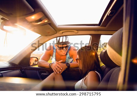 Happy couple enjoying on a long drive in a car. Friends going on road trip on summer day. Caucasian young man driving a car and joyful woman with her arms raised.hipster friends,swag,sunlight,caps - stock photo
