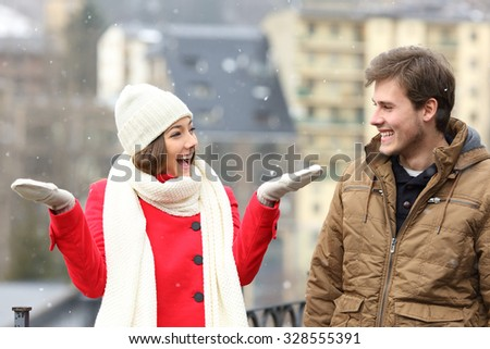 Happy couple enjoying snow in a snowy day in the street of a town - stock photo