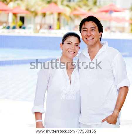 Happy couple enjoying their holidays at a resort - stock photo