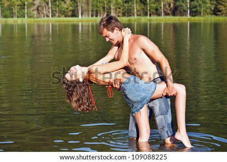 Happy couple enjoying their time together in the montain lake - stock photo