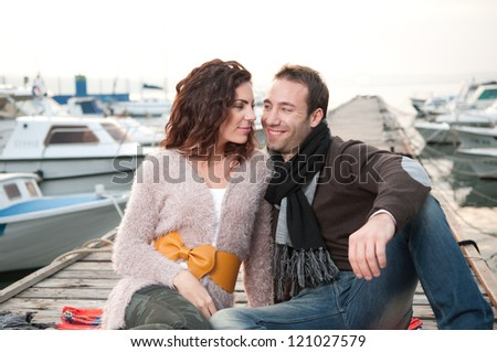 Happy couple enjoying time together. Sitting on wooden pier. - stock photo