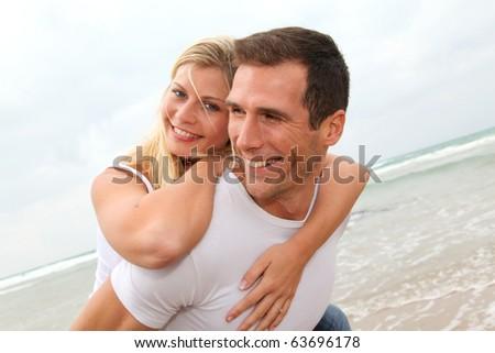 Happy couple enjoying vacation on a sandy beach - stock photo